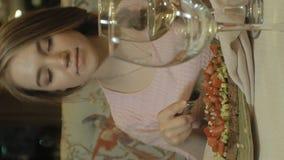 Vídeo vertical Mujer rubia hermosa que come y que bebe en el restaurante, hora de la almuerzo metrajes