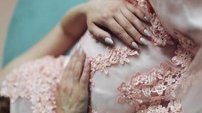 Vídeo vertical Mulher gravida nova bonita que senta-se em um sofá que olha na câmera e nas posses suas mãos nela filme