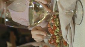 Vídeo vertical Mulher loura bonita que come e que bebe no restaurante, pausa para o almoço filme