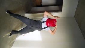 Vídeo vertical O trabalhador no uniforme com a cubeta vermelha em sua cabeça tem o divertimento e a dança video estoque