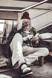 Vídeos de assento e de observação do preguiçoso relaxado no telefone fotografia de stock