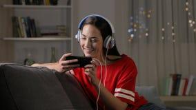 Vídeos de observación adolescentes en el teléfono en la noche en un sofá almacen de metraje de vídeo