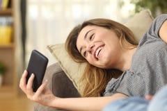 Vídeos de observación adolescentes en un teléfono elegante en casa Fotografía de archivo libre de regalías