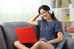 Vídeos de observación adolescentes felices en línea en casa Imagen de archivo
