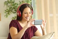 Vídeos de observación de la muchacha en un teléfono elegante con los auriculares Fotos de archivo libres de regalías