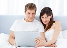 Vídeos de observación de los pares jovenes en su ordenador Imágenes de archivo libres de regalías