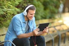Vídeos de observación de relajación del individuo en línea en una tableta Foto de archivo libre de regalías
