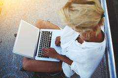 Vídeos de observación del adolescente femenino en el red-libro portátil mientras que disfruta del verano que iguala al aire libre Imagen de archivo