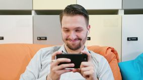Vídeos de observación del hombre en el smartphone dentro fotografía de archivo libre de regalías