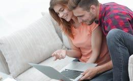 Vídeos de observación de los pares jovenes en el ordenador portátil Foto de archivo