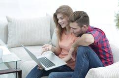 Vídeos de observación de los pares jovenes en el ordenador portátil Fotos de archivo libres de regalías