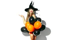 Víspera de Todos los Santos Bruja atractiva que sostiene los balones de aire fotos de archivo