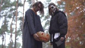 Víspera de Todos los Santos El individuo y la muchacha con el maquillaje de Halloween en el bosque almacen de video