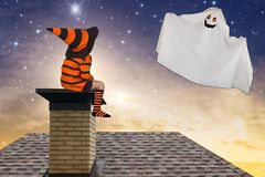 Víspera de Todos los Santos El muchacho en los disfraces de Halloween que se sientan en el tejado y mira para arriba el fantasma  imagen de archivo