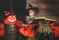 Víspera de Todos los Santos el niño de la bruja conjura con el libro de encantos, de la vara mágica y de calabazas Fotografía de archivo