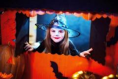 Víspera de Todos los Santos feliz Una pequeña muchacha hermosa en un traje de la bruja celebra con las calabazas fotografía de archivo libre de regalías