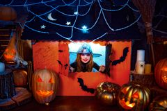 Víspera de Todos los Santos feliz Una pequeña muchacha hermosa en un traje de la bruja celebra con las calabazas foto de archivo