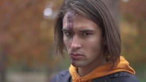 Víspera de Todos los Santos Individuo de Youmg con un maquillaje asustadizo de Halloween almacen de metraje de vídeo