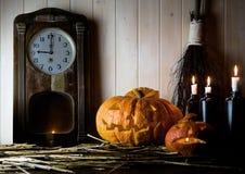 Víspera de Todos los Santos Interior del vintage en estilo occidental velas, reloj antiguo, escoba y calabaza que brilla intensam Fotos de archivo