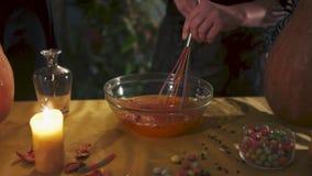 Víspera de Todos los Santos La mano femenina mezcla el líquido con un batir Todos los santos Eve almacen de metraje de vídeo