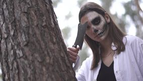 Víspera de Todos los Santos Muchacha con un cuchillo y un maquillaje de Halloween que ocultan detrás de un árbol almacen de metraje de vídeo