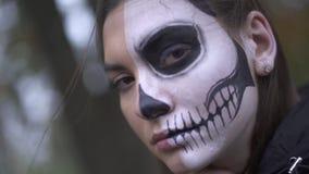 Víspera de Todos los Santos Muchacha con un maquillaje asustadizo en el piso de la cara almacen de metraje de vídeo