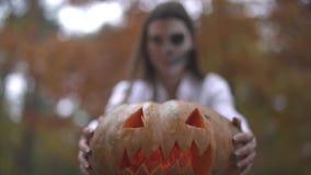 Víspera de Todos los Santos Muchacha con un maquillaje asustadizo de Halloween que sostiene una calabaza en sus manos almacen de video