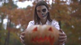 Víspera de Todos los Santos Mujer con un maquillaje asustadizo de Halloween que sostiene una calabaza en sus manos almacen de metraje de vídeo