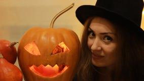 Víspera de Todos los Santos Mujer en el sombrero negro con las calabazas Ascendente cercano del retrato almacen de video