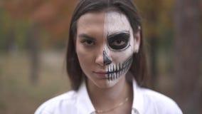 Víspera de Todos los Santos Mujer sonriente con maquillaje muerto del hombre metrajes