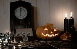 Víspera de Todos los Santos naipes, reina de espadas, velas, calabazas y el reloj viejo en el fondo de madera Imagen de archivo