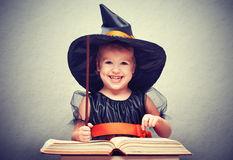 Víspera de Todos los Santos pequeña bruja alegre con el conjur mágico de la vara y del libro fotos de archivo libres de regalías