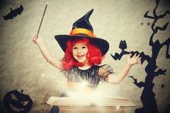 Víspera de Todos los Santos pequeña bruja alegre con el conjur mágico de la vara y del libro Foto de archivo