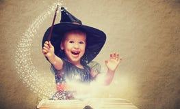 Víspera de Todos los Santos pequeña bruja alegre con una vara mágica y un b que brilla intensamente imagen de archivo