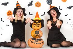 Víspera de Todos los Santos Retrato de la mujer joven dos en disfraces de Halloween negros de la bruja en partido Foto de archivo libre de regalías
