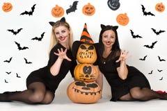 Víspera de Todos los Santos Retrato de la mujer joven dos en disfraces de Halloween negros de la bruja en partido Imagen de archivo libre de regalías
