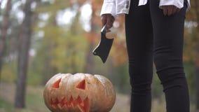Víspera de Todos los Santos Una muchacha con un cuchillo se está colocando sobre una calabaza de Halloween metrajes