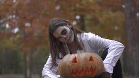 Víspera de Todos los Santos Una muchacha con un maquillaje asustadizo de Halloween se está sentando cerca de la calabaza almacen de metraje de vídeo