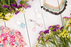 vístase, las flores coloridas, maquillaje de los cosméticos, joya y esencial en el fondo de madera blanco Imagen de archivo libre de regalías