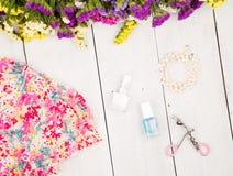 vístase, las flores coloridas, maquillaje de los cosméticos, joya y esencial en el fondo de madera blanco Imagenes de archivo