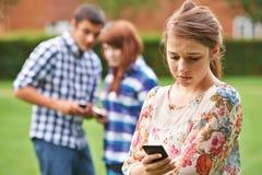 Vítima do adolescente de tiranizar pela mensagem de texto fotografia de stock