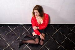 Vítima do ser humano que trafica que senta-se no assoalho Foto de Stock