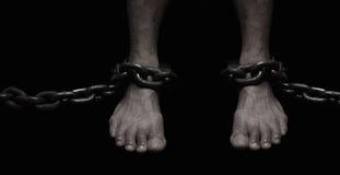 Vítima, escravo, foor masculino do prisioneiro amarrado pela corrente grande do metal Peopl Imagens de Stock