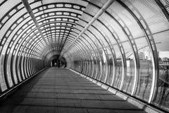 Vórtice como el puente peatonal construido con el vidrio y acero y dos Imagen de archivo