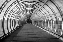 Vórtice como el puente peatonal construido con el vidrio y acero y dos Fotos de archivo