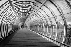 Vórtice como el puente peatonal construido con el vidrio y acero y dos Foto de archivo