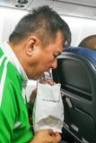 Vômito asiático nauseabundo do homem da doença de ar no saco da doença de ar Foto de Stock Royalty Free