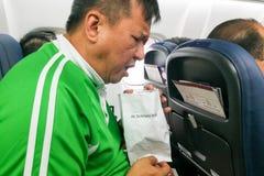Vômito asiático nauseabundo do homem da doença de ar no saco da doença de ar Imagem de Stock