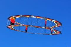 Vôo circular do papagaio em um céu azul fotografia de stock royalty free