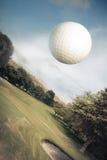Vôo da esfera de golfe sobre um campo verde Imagem de Stock
